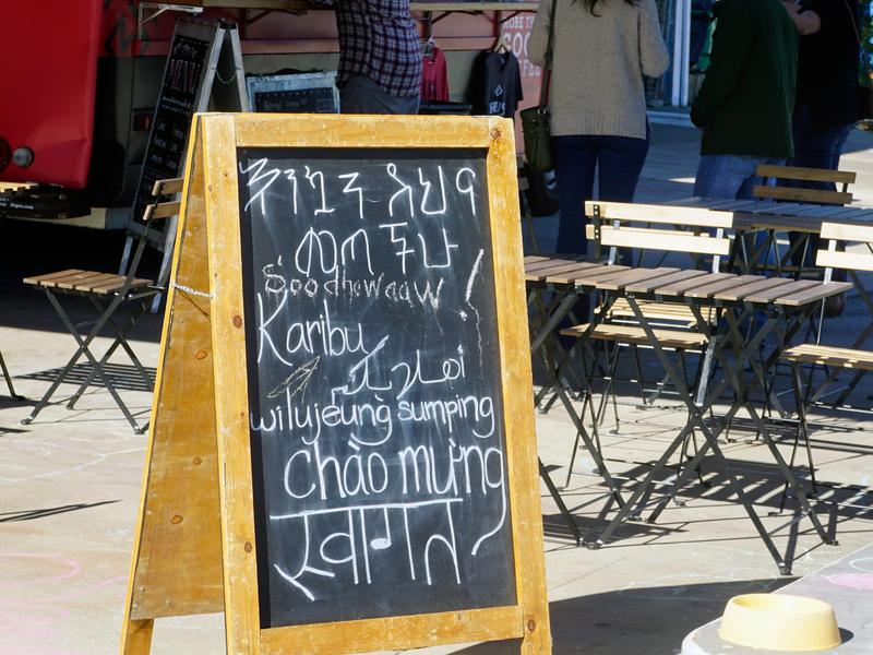 """A sign outside the Refuge Coffee food truck says """"Welcome"""" in (top to bottom) Amharic, Somali, Swahili, Arabic, Sudanese, Vietnamese and Nepali."""