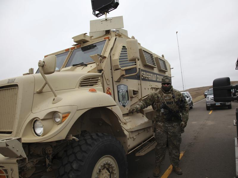 A member of the Stutsman County SWAT team who declined to give his name nor to be identifiable by badge stands guard by an armored personnel carrier equipped with an LRAD, or long range acoustic device, while deployed to watch protesters demonstrating against the Dakota Access Pipeline.