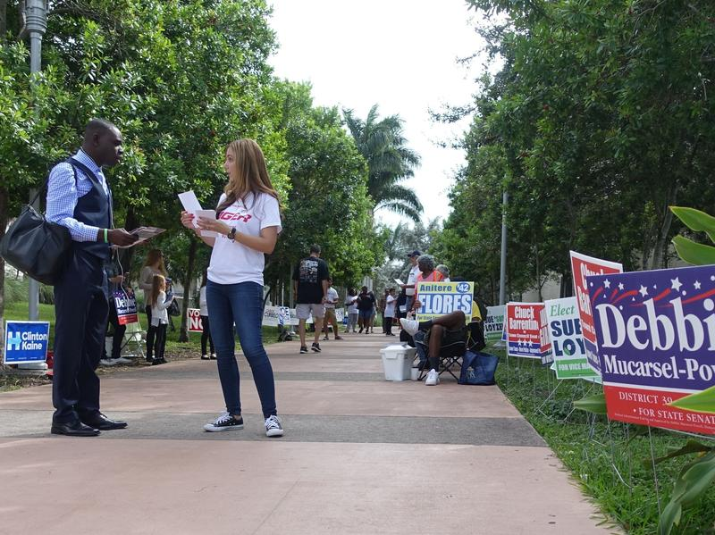 Marcela Stewart speaks to a voter at an event to encourage minority voter turnout n Cutler Bay, Fla., on Sunday.