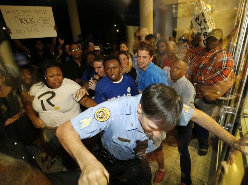 A police officer keeps protesters at bay before a debate for Louisiana candidates for the U.S. Senate at Dillard University in New Orleans Wednesday night.