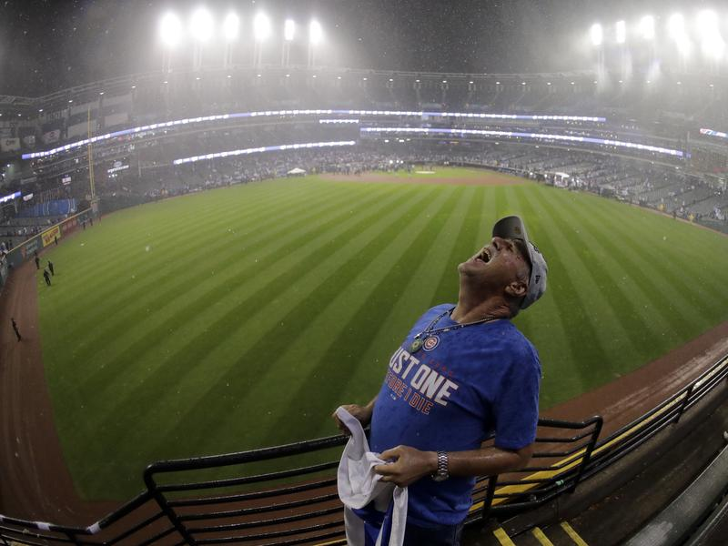 """An unnamed Chicago Cubs fan catches raindrops in his mouth after the Cubs finally won the World Series on Wednesday. His shirt says, """"Just one before I die."""""""