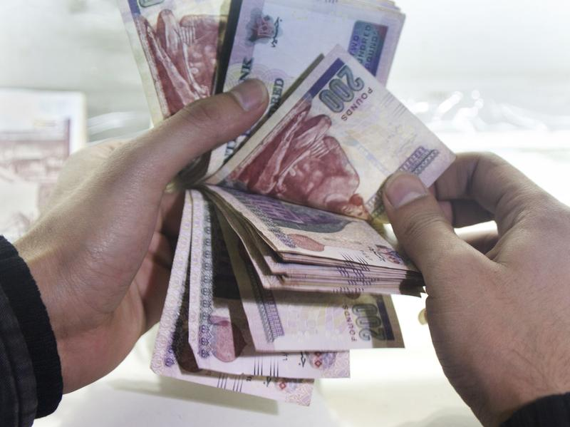 A man counts Egyptian currency at an exchange office in Cairo.