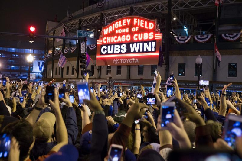 Chicago fans celebrate the Chicago Cubs 8-7 victory over the Cleveland Indians in Cleveland in 10th inning in game seven of the 2016 World Series, outside Wrigley Field in Chicago, Illinois early on Nov. 3, 2016. (Tasos Katopodis/Getty Images)