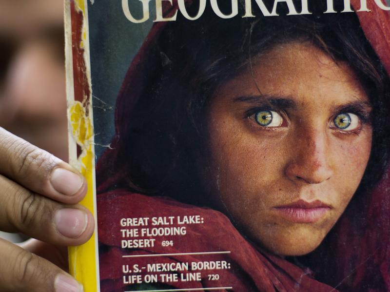 The owner of a bookstore shows a copy of <em>National Geographic</em> magazine with the 1984 photograph of Sharbat Gula in Islamabad, when she was around 12 years old.