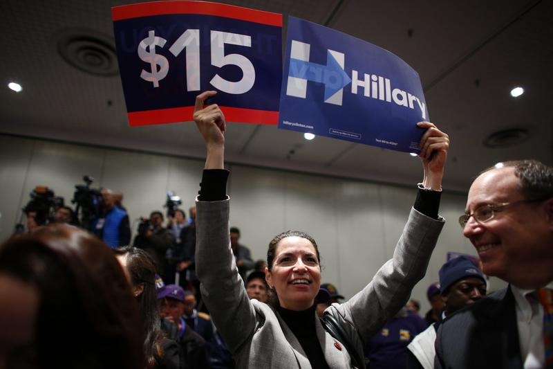 A woman holds banners in support of a $15 minimum wage as Democratic presidential candidate Hillary Clinton speaks during a event at the Javitz Center in New York on April 4, 2016. (Kena Betancur/AFP/Getty Images)