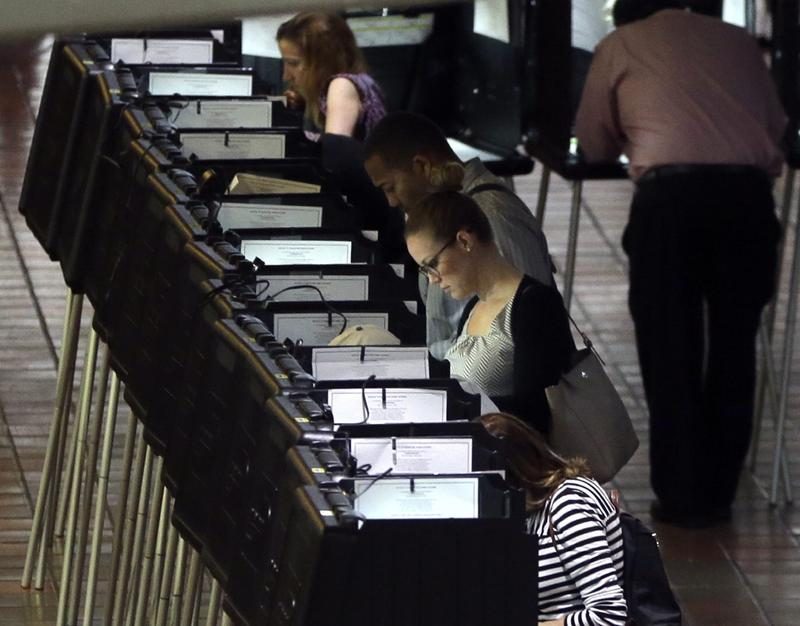 In this Oct. 24, 2016 file photo, people vote at a polling station on the first day of early voting in Miami-Dade County for the general election in Miami. Florida (Lynne Sladky/AP)