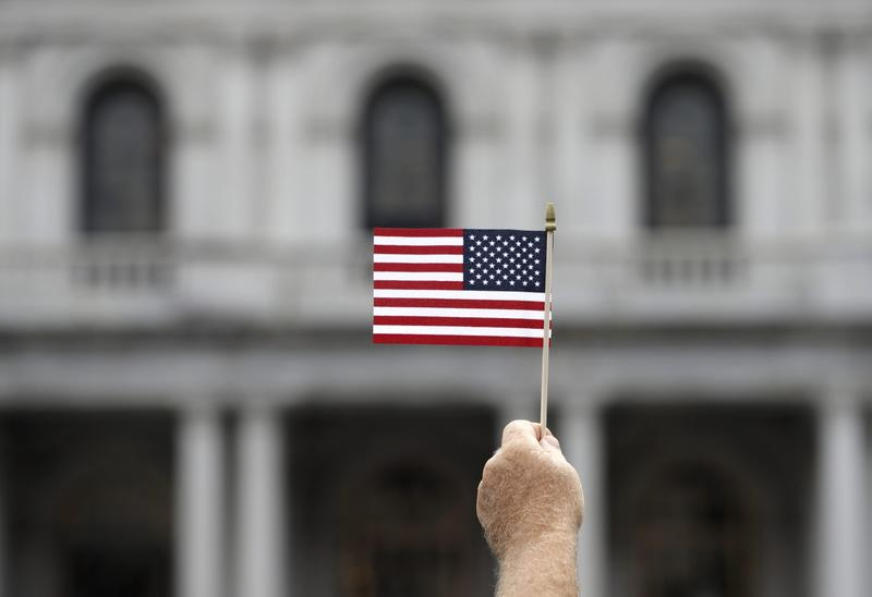 A man holds a flag during an election prayer rally in Albany, N.Y., in August. (Mike Groll/AP)