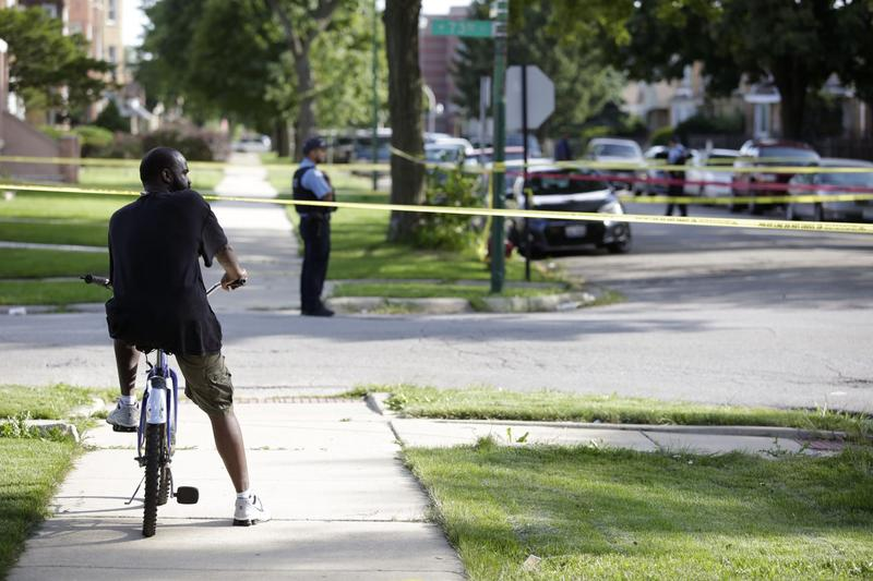 A man on his bike looks at a crime scene where a man was fatally shot on Aug. 31, 2016 in Chicago. (Joshua Lott/Getty Images)