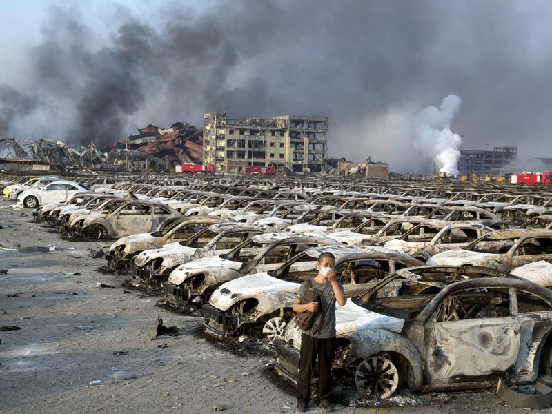 A man stands near the charred remains of new cars at a parking lot near the site of the warehouse explosions in Aug. 2015, in northeastern China's Tianjin municipality.