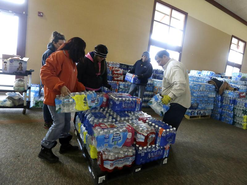 Volunteers load a pallet with bottled water to be distributed outside Our Lady of Guadalupe Church in Flint, Mich., in February.