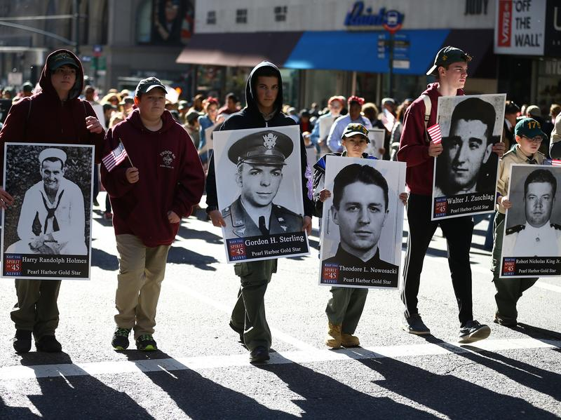 "People attend the Veterans Day Parade in New York City Thursday. Known as ""America's Parade,"" it features over 20,000 participants, including veterans of numerous eras, military units, businesses and high school bands and civic and youth groups."