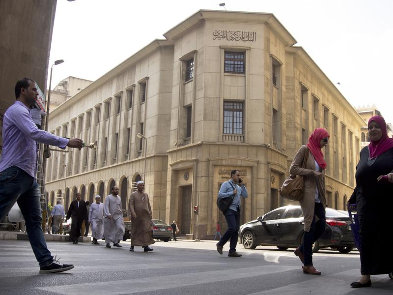 Egyptians walk in front of the Central Bank earlier this month in Cairo.