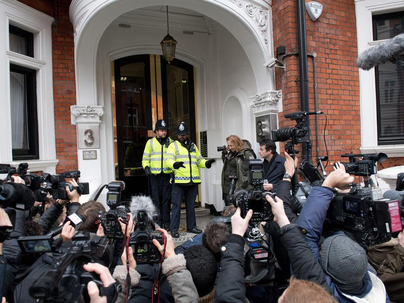Police officers are surrounded by media as they stand outside the Ecuadorean Embassy in London on Monday, where WikiLeaks founder Julian Assange was set to be questioned over a rape allegation against him.