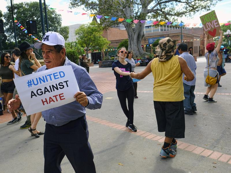 "A man carrying a sign that reads ""United Against Hate"" dances with other demonstrators during a protest against President-elect Donald Trump in Olvera Street's Plaza in downtown Los Angeles on Saturday."