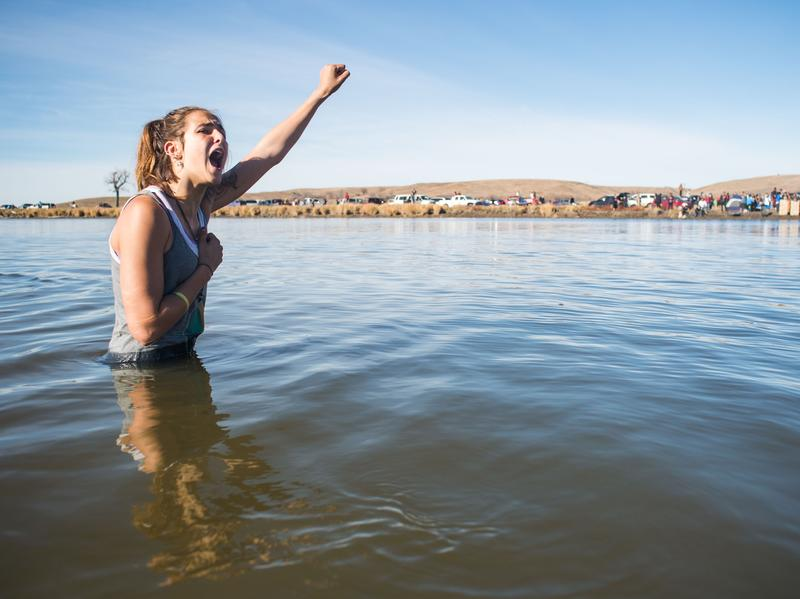 Demonstrator Stephanie Jasper stands in the Cannonball River during a standoff with police at Turtle Island, north of the Standing Rock Sioux Reservation.