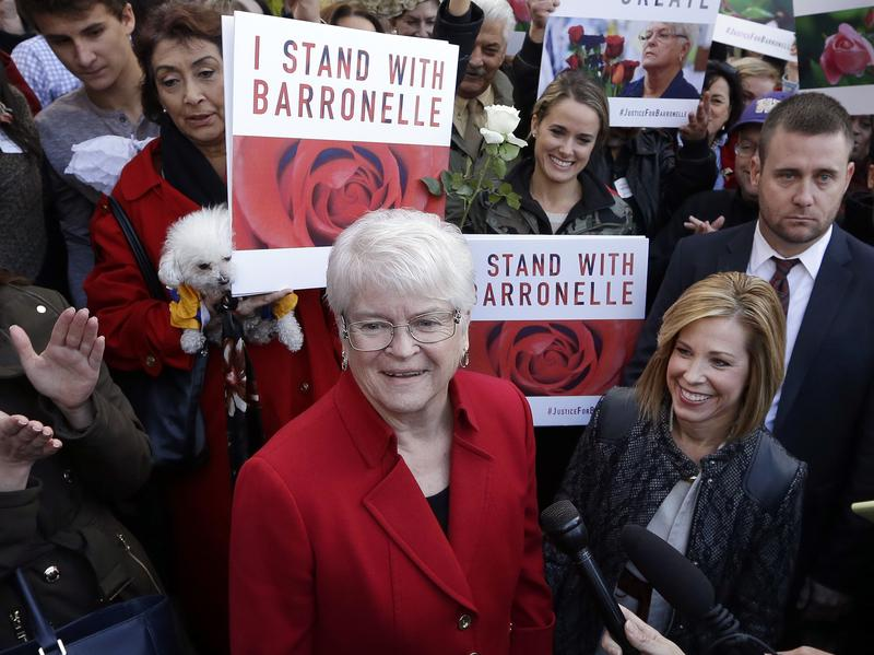Barronelle Stutzman, center, a Richland, Wash., florist who was fined for denying service to a gay couple in 2013, is surrounded by supporters after a hearing before Washington's Supreme Court, on Tuesday,  in Bellevue, Wash.