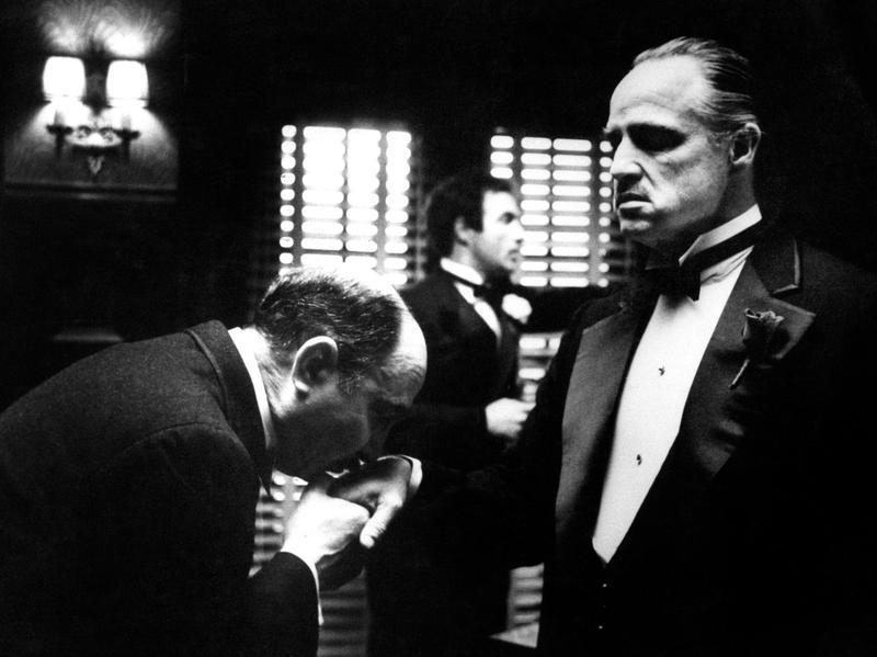 Amerigo Bonasera (Salvatore Corsitto) kisses the hand of Don Vito Corleone (Marlon Brando) in a scene from Francis Ford Coppola's <em>The Godfather</em>.