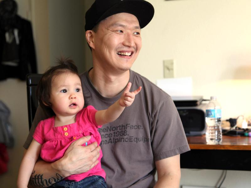 South Korean adoptee Adam Crapser poses with his 1-year-old daughter, Christal, in the family's living room in Vancouver, Wash., in 2015. Crapser, who was flown to the U.S. nearly 40 years ago and adopted by an American couple at age 3, has been ordered deported to South Korea.