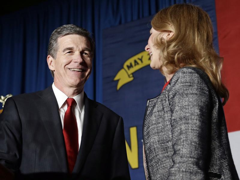 Democratic challenger Roy Cooper has a lead of more than 6,000 votes over Gov. Pat McCrory. He's seen here with his wife, Kristin, at an election night rally in Raleigh.
