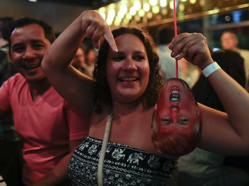 A woman at a bar in Buenos Aires, Argentina, laughs as she holds a mask depicting Donald Trump during an election night party on Nov. 8.