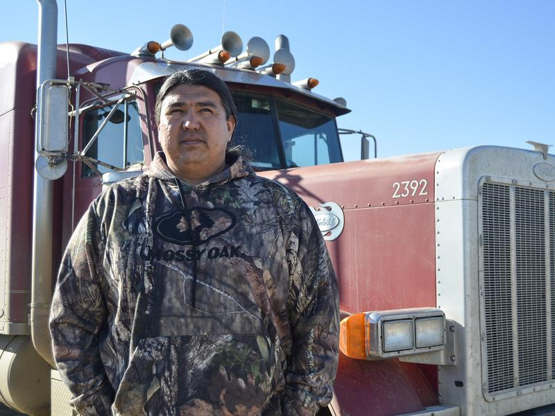 T.J. Plenty Chief stands in front of one of the three semitrucks owned by his company, Red Road Trucking. The trucks operate in the Fort Berthold reservation oil fields, carrying everything from gravel to pipe to water needed for drilling. His business is based on the reservation, in New Town, N.D., where he lives.