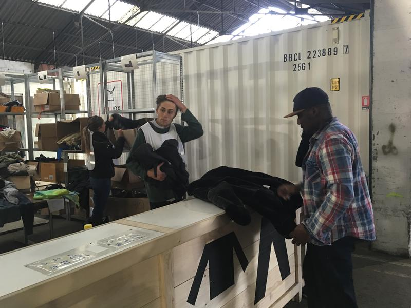 A recently arrived migrant (right) receives clothes at Paris welcome center for migrants that opened earlier this month. They can stay for up to 10 days, but are then moved to migrant centers around the country.