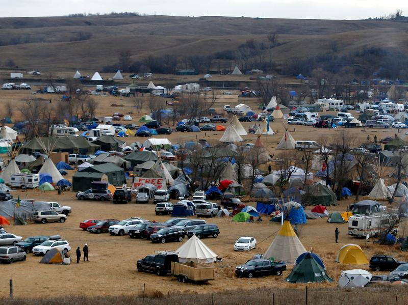 Protesters — or water protectors, as they identify themselves — walk along Highway 1806, past a sprawling encampment at Standing Rock on Thursday. Thousands of people gathered to join the Standing Rock Sioux Tribe's protest of the Dakota Access Pipeline.