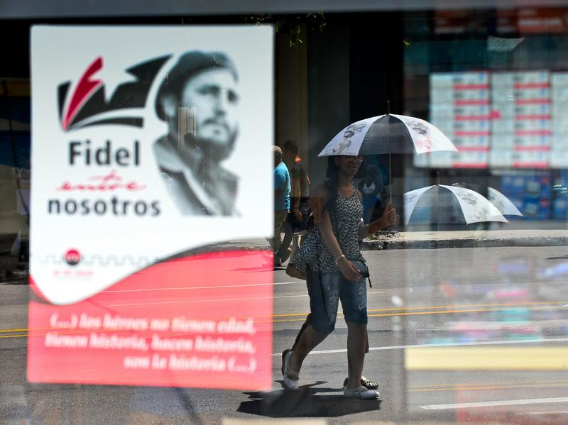 A woman walks next to a poster about Cuban former president Fidel Castro, on August 13, 2016, in Havana.