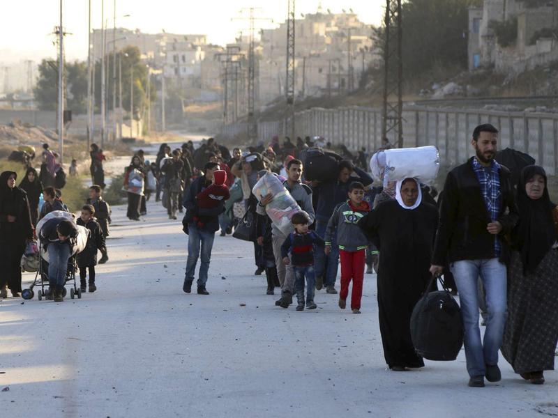People flee rebel-held eastern neighborhoods of Aleppo into the Sheikh Maqsud area, controlled by Kurdish fighters, in Syria on Sunday. The photo was provided by the Rumaf, a Syrian Kurdish activist group, and authenticated by The Associated Press.