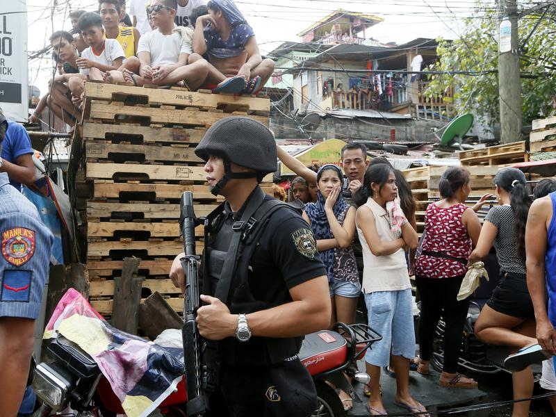 A police SWAT team member stands guard while residents watch the body of a person killed in an alleged police anti-drug operation in Manila on Nov. 10.