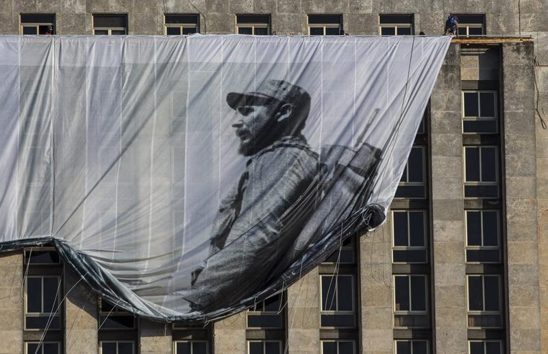 Men hang a giant banner with a picture of Cuba's late leader Fidel Castro as a young revolutionary, from the Cuban National Library building in Havana, Cuba, Sunday, Nov. 27, 2016. (Desmond Boylan/AP)