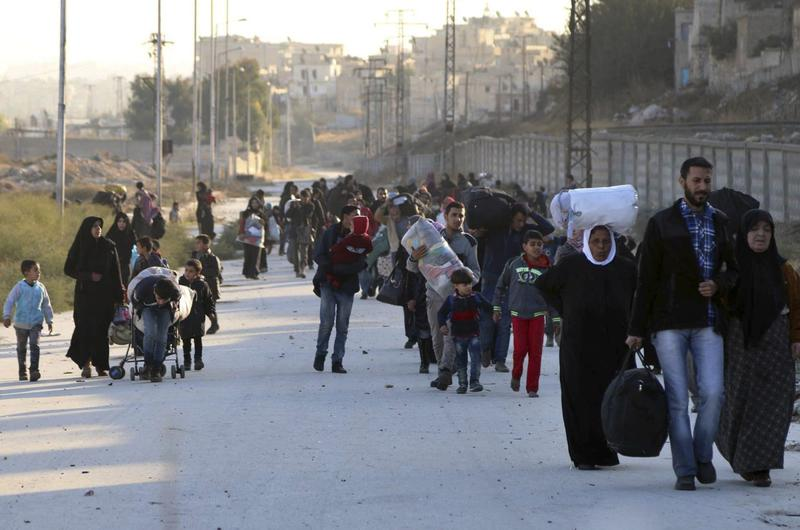 This Sunday, Nov. 27, 2016 photo provided by the Rumaf, a Syrian Kurdish activist group, which has been authenticated based on its contents and other AP reporting, shows people fleeing rebel-held eastern neighborhoods of Aleppo into the Sheikh Maqsoud area that is controlled by Kurdish fighters. (The Rumaf via AP)
