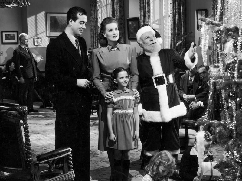 (Left to right) Actors John Payne, Maureen O'Hara, Edmund Gwenn, and young Natalie Wood stand before a Christmas tree in a still from director George Seaton's film, <em>Miracle on 34th Street</em>.