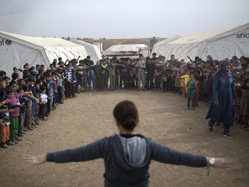 Iraqi children follow instructions given by a teacher (center) during an outdoor class at the Hassan Sham camp on Nov. 10.