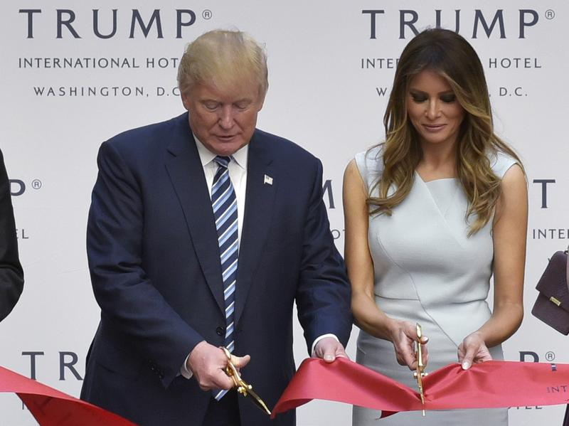 Donald Trump, along with his wife, Melania, and son Eric, cuts the ribbon during the grand opening ceremony for the Trump International Hotel, located in the Old Post Office building in Washington, D.C. The building, which is owned by the General Services Administration, is leased to the Trump family.