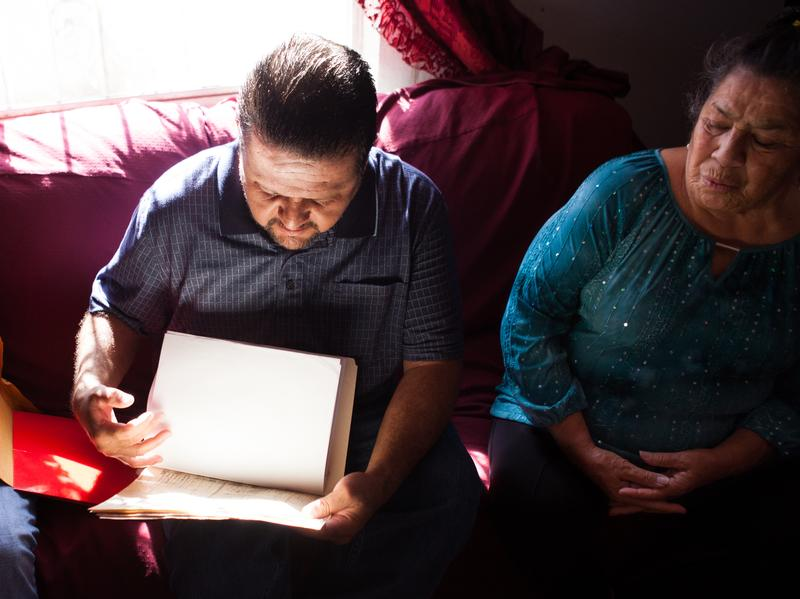 Lorenzo Palma (center) reviews family documents with his brother and mother in their home in El Paso, Texas. Palma served time for a parole violation and, just as he was being released, was sent before an immigration court to prove his U.S. citizenship.