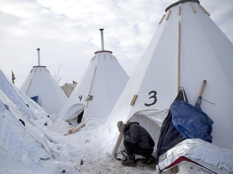 """Jacob Brooks makes adjustments to one of the camp's many """"tarpees,"""" a winterized teepee made of tarp with a built-in chimney, designed by Paul Cheokoten Wagner. There are roughly 60 tarpees around various camps now, and Wagner has fundraised enough for another 20 more."""