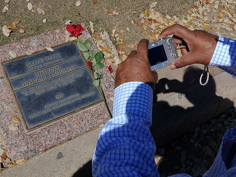 A tourist photographs a historic landmark plaque, on March 13, 2010, in front of the Grassy Knoll and beside the former Texas School Book Depository Building in Dealey Plaza where the 1963 assassination of President John F. Kennedy took place in Dallas, Texas.