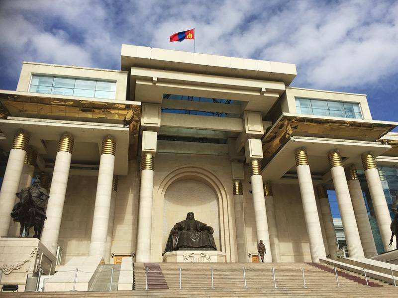 A statue of Genghis Khan sits atop the stairs of the Government Palace in Ulaanbaatar, Mongolia's capital. The country's economy has slowed down since the drop in gold and mineral prices.