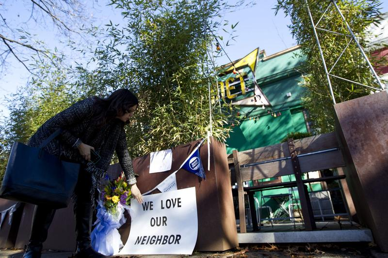 "Meighan Stone places a support banner with flowers outside the door of Comet Ping Pong pizza shop, in Washington, Monday, Dec. 5, 2016. A fake news story prompted a man to fire a rifle inside the popular Washington, D.C., pizza place as he attempted to ""self-investigate"" a conspiracy theory that Hillary Clinton was running a child sex ring from there, police said.  (Jose Luis Magana/AP)"