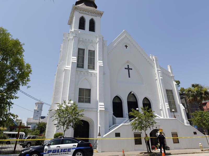Police officers stand in front of the Emanuel AME Church in Charleston, S.C. Jurors on Thursday saw horrific photos of the church basement at the trial of Dylann Roof, accused of hate crimes in the killings of nine black people at the church last year.