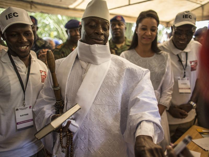 Gambian president Yahya Jammeh (center) has his finger inked before casting his marble in a polling station in a presidential poll, in Banjul on Dec. 1, 2016.
