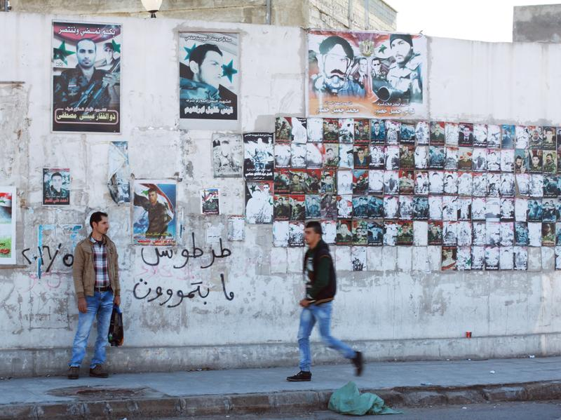 "A wall in Tartus is covered in posters commemorating the lives of men who died fighting on Assad's side. Graffiti on the wall says, ""Tartus doesn't die."""