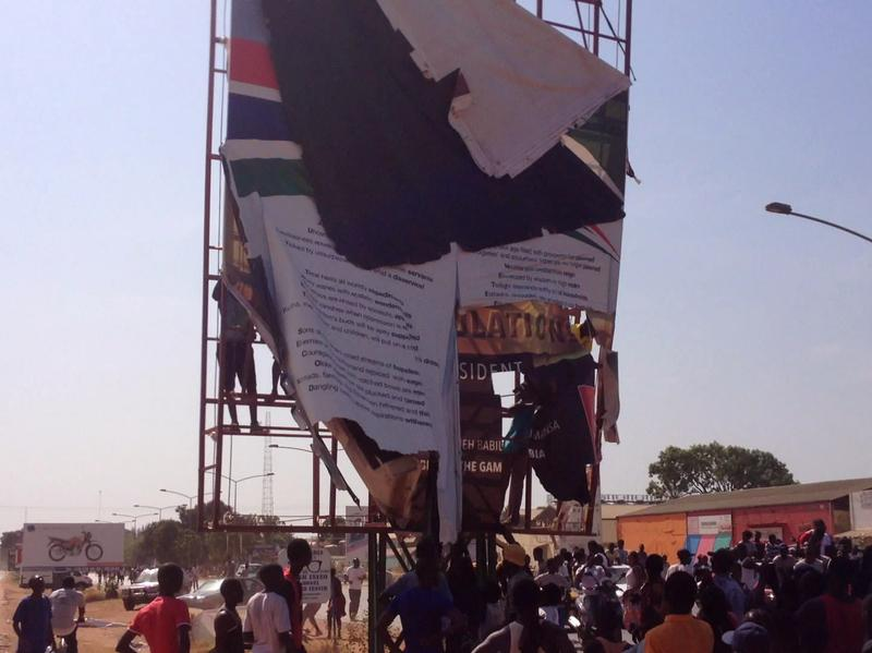 An election billboard promoting Gambian President Yahya Jammeh as part of his election campaign is removed by supporters of president-elect Adama Barrow on Saturday in Banjul, Gambia.
