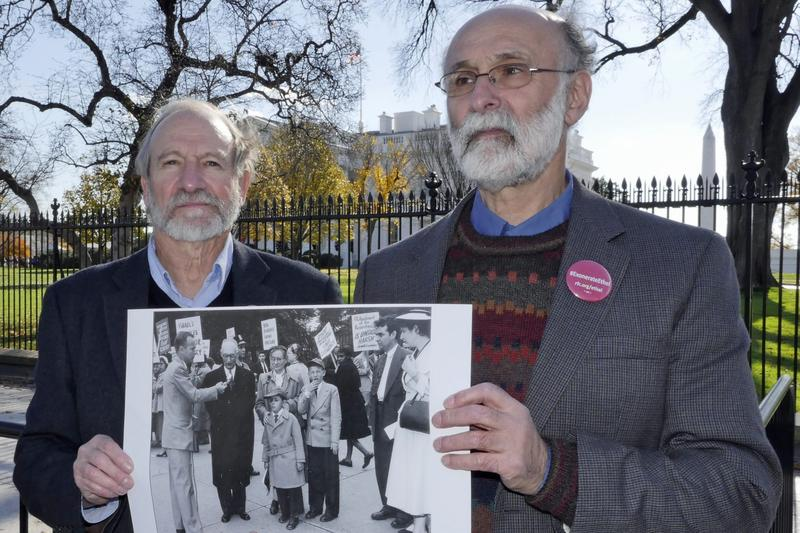 Michael (left) and Robert Meeropol demonstrating outside the White House on Dec. 1, 2016, holding a photograph of themselves demonstrating as children in 1953. (Courtesy Alan Heath/Rosenberg Fund for Children)