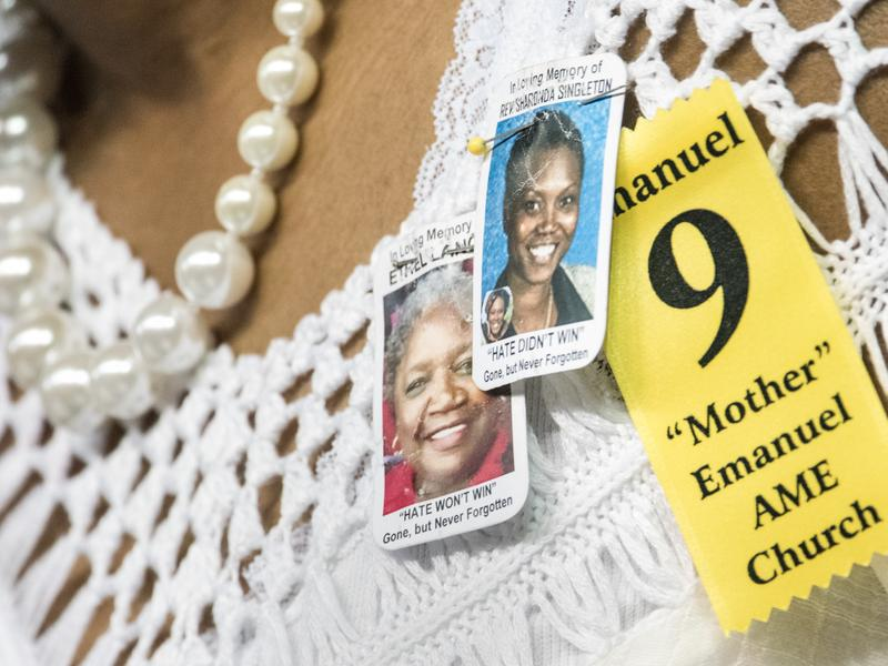 A woman at a memorial service wears tributes to two of the nine people murdered at Charleston's Emanuel African Methodist Episcopal Church, Sharonda Singleton and Ethel Lance.