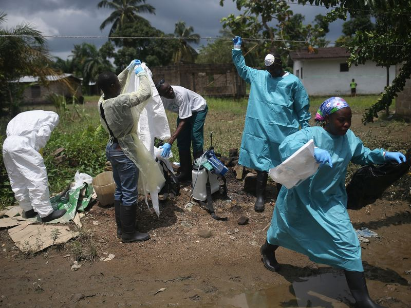 An Ebola burial team dons protective clothing before collecting the body of a woman who'd died from the virus in her home in a suburb of Monrovia, Liberia's capital.