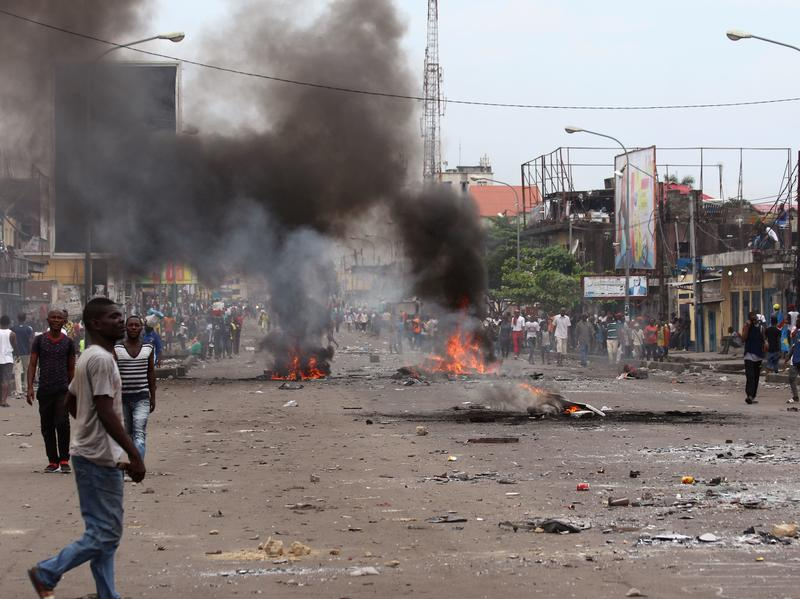 A man crosses a road near burning debris during September's election protests in Kinshasa, Democratic Republic of Congo.