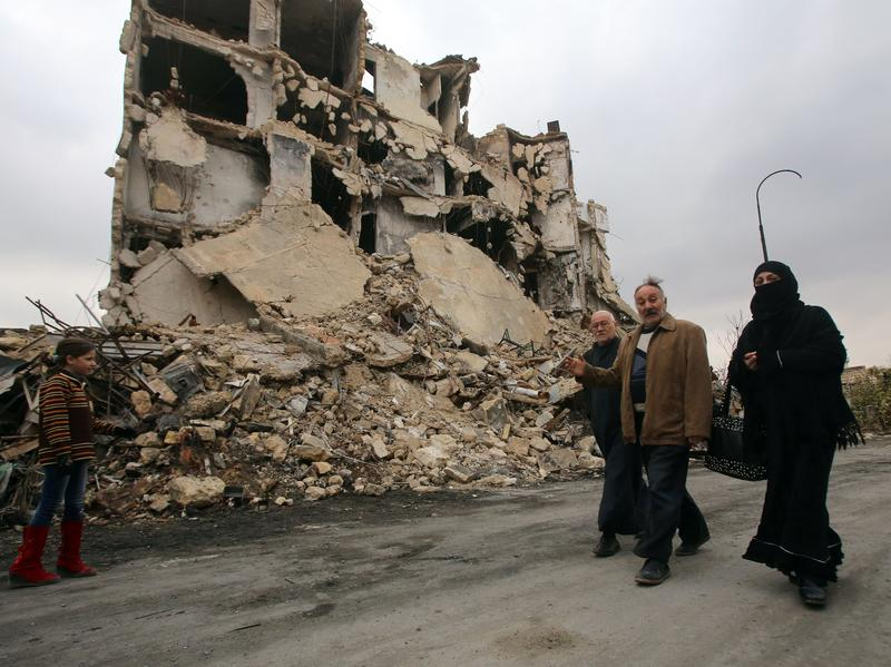 Syrians walk in the old city of Aleppo Saturday, as pro-government forces worked to re-open previously barricaded roads. Civilians and rebel fighters are trying to leave the city's eastern half.