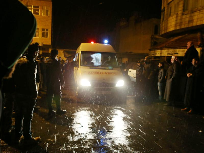 An ambulance leaves the scene following a gun attack in Karak, Jordan, Sunday. A Canadian tourist is among at least 10 people who died in a shootout between police and gunmen.